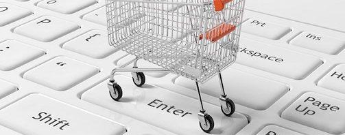Shopping cart on white laptops keyboard